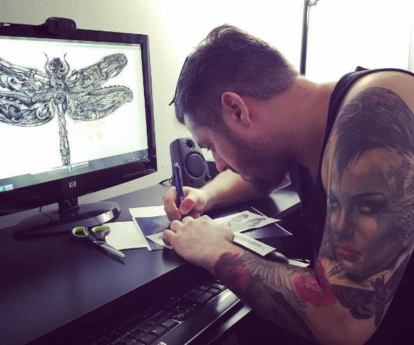 CHICAGO Infamous Ink tattoo artist Josh Meadows tediously preparing the dragonfly design for FRAUDSTER Jorge Cadenas body art. 2016 All rights reserved. IDTheftReport2020.com